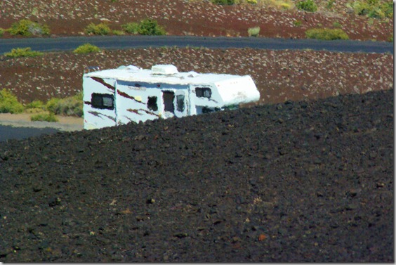 Class C Motorhome seen through heated air rising off of black cinders on Inferno Cone at Craters of the Moon National Monument