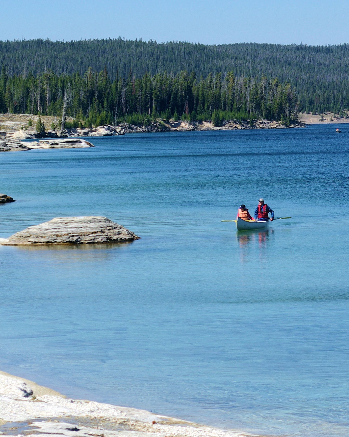 Canoe along shore of lake yellowstone next to fishing cone for Yellowstone lake fishing